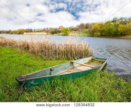 old wooden boat in grass near river