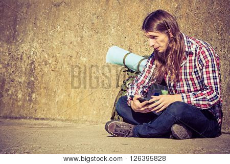 Man tourist backpacker relaxing outdoors sitting by grunge wall using tablet. Internet tourism active lifestyle. Young hipster guy tramping.