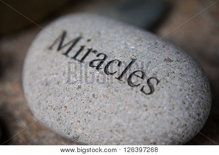 pebble with engraved message miracles. Inspirational stones
