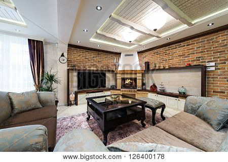 Apartment interior with fireplace and big brick wall