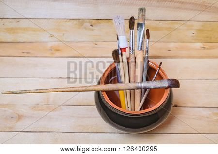 Artistic brushes in a clay pot on a wooden background