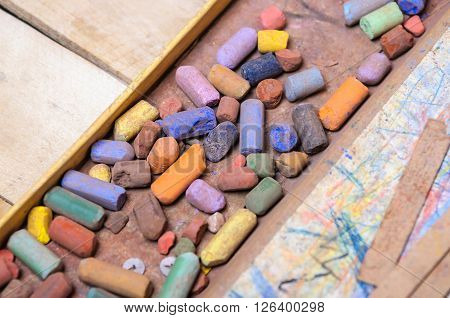 Open box with the remains of the old chalk pastels assorted colors