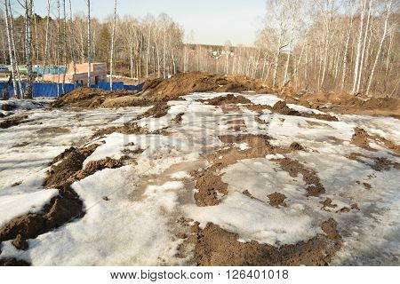 Muddy spring road leading to construction area. Preparing to Siberian Spartakiad. Photo made in Russian Sibiria, Krasnoyarsk.