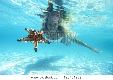 Woman is snorkeling underwater, showing starfish