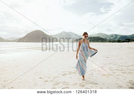 Woman wearing ethnic flying dress walking barefoot at the beach, Lombok, Indonesia