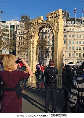 LONDON UK - APRIL 19 2016: Crowds photographing and enjoying a recreation of the Arch of Triumph from Syria's ancient city of Palmyra. The arch has been recreated by 3D printing and will travel the world.