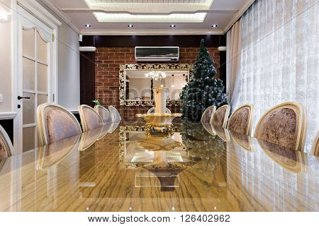 Dining room interior in modern bright apartment and Christmass tree