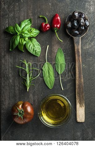 Vegetables and herbs on dark rustic wooden background. Greek black olives, fresh green sage, rosemary, basil herbs, oil, tomato, peppers.  Top view