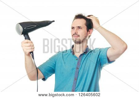 The adult man with a beard in a blue shirt dries hair the hair dryer.