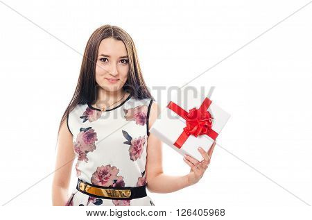 The beautiful girl in a dress holds a gift in hand and smiles