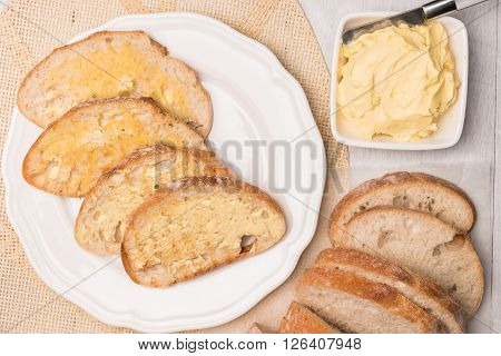 Fresh bread and homemade butter on wooden background. Top view with copy space.