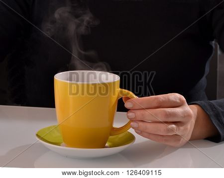 Hand holding hot coffee cup and smoke.