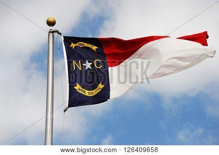 North Carolina State flag waving under sky