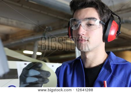 Worker with anti-noise headphones and goggles