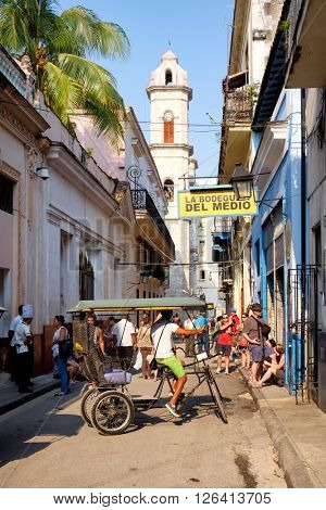 HAVANA,CUBA- MARCH 15,2016 : Tourists and cubans next to the famous Bodeguita del Medio and the Cathedral Church in Old Havana