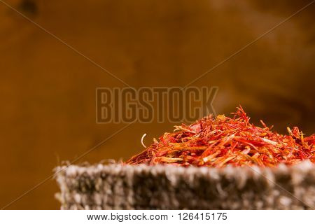 Spices saffron in a bag on a wooden background
