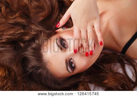 Young sexy woman in bra lying on the bed. She covers her mouth with her hand. Bliss. Girl flirts. Close-up portrait.