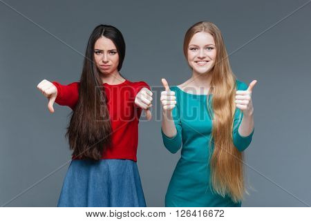 Woman showing thumb down and her girlfriend showing thumb up over gray background
