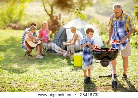 happy family on camping making barbecue