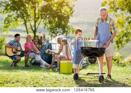 grandson grilling with grandfather on camping