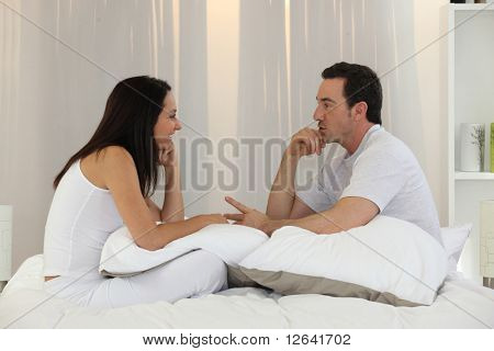 Couple talking in bedroom