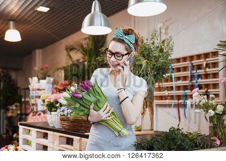 Cheerful attractive young woman florist holding two bunches of tulips and talking on mobile phone in flower shop
