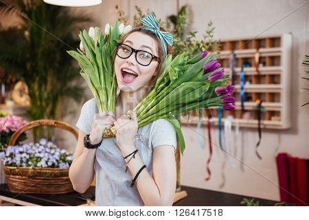 Funny happy young woman florist holding two bunches of tulips in flower shop