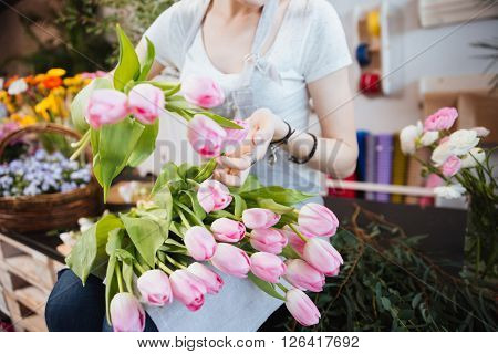 Closeup of young woman florist sitting and taking care of pink tulips in flower shop