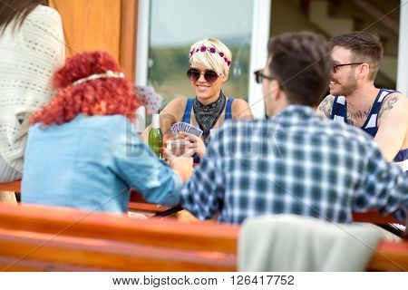Guys and lassies in nice spring day in restaurant outdoor play cards, drinks beer and makes joke
