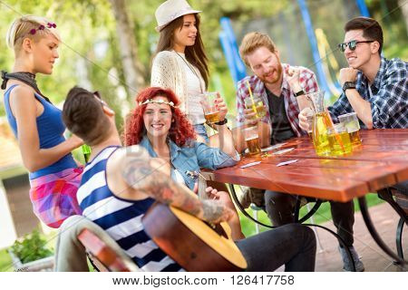 Guys and lassies spend sunny day in open in good mood with drinks and good guitar music