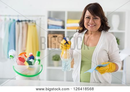 Smiling mature housewife ready to clean the house