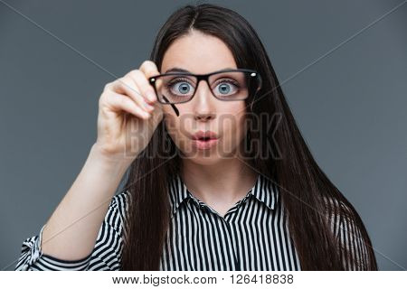 Funny woman holding glasses and looking at camera over gray background