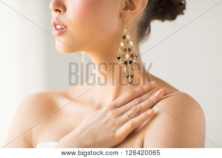 glamour, beauty, jewelry and luxury concept - close up of beautiful woman with earrings