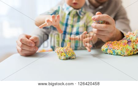 family, childhood, creativity, activity and people concept - close up of happy father and little son playing with ball clay at home