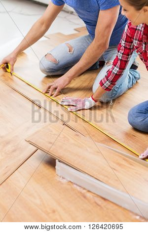 repair, building, flooring and people concept - close up of happy couple with ruler measuring parquet board at home