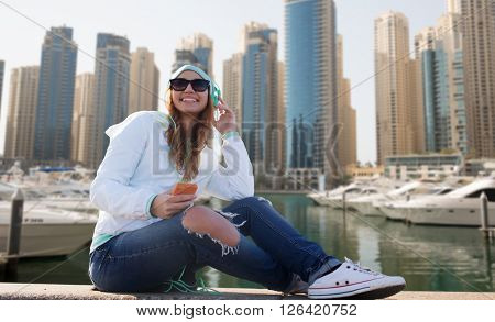 technology, lifestyle and people concept - smiling young woman or teenage girl with smartphone and headphones listening to music over dubai city street or waterfront with boats background