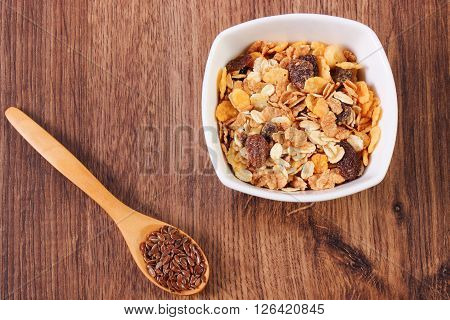 Portion of muesli in glass bowl and linseed on spoon concept of healthy nutrition, ingredients with dietary fiber