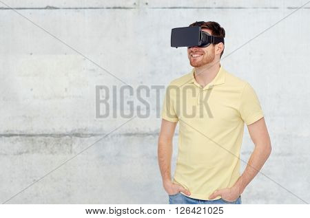 3d technology, virtual reality, entertainment and people concept - happy young man with virtual reality headset or 3d glasses over concrete gray wall background