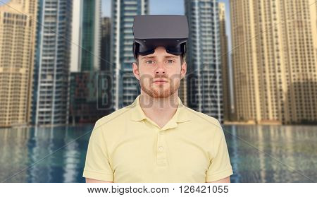 3d technology, virtual reality, entertainment and people concept - young man with virtual reality headset or 3d glasses over dubai city infinity edge pool background