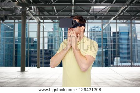 3d technology, virtual reality, entertainment and people concept - amazed young man with virtual reality headset or 3d glasses playing game over empty industrial room and city panorama background