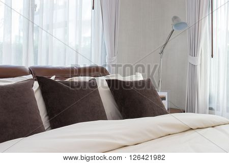 Modern Bedroom With Brown Pillows And Lamp