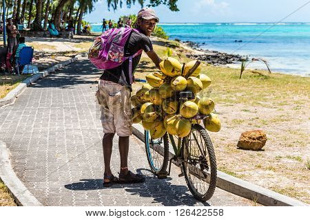 Blue Bay Mauritius - December 27 2015: Mauritius young man selling coconuts from his bike on the beach Blue Bay Mauritius.