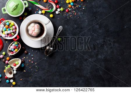Colorful candies and coffee cup on stone background. Top view with copy space