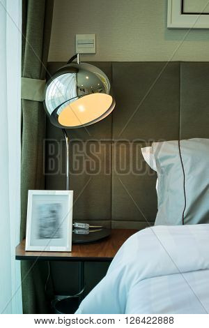 Metal Desk Lamp And Grey Pillow On Bed