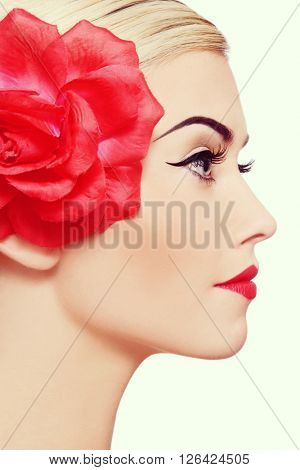 Vintage style profile portrait of young beautiful blond woman with winged eye make-up and red flower in hair