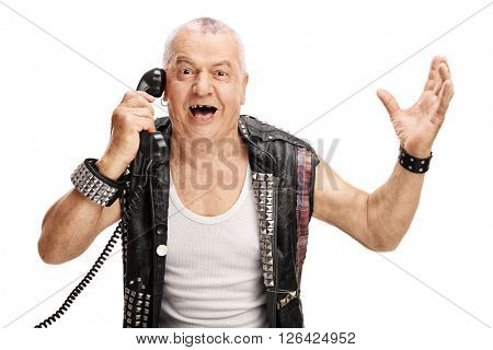 Mature man in an old punk jacket talking on telephone and gesturing with his hands isolated on white background