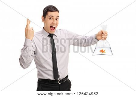 Young man holding a goldfish in a plastic bag and crossing his fingers isolated on white background