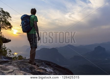 Hiker with rucksack standing on the mountain and looking at the sunrise