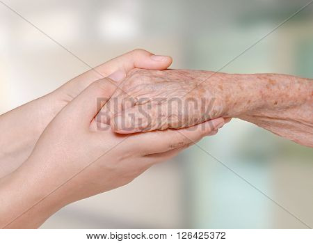 Young woman's hand holding olderly's hand in hospital