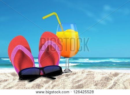 Slipper with sungalsses and orange drinks on a beach